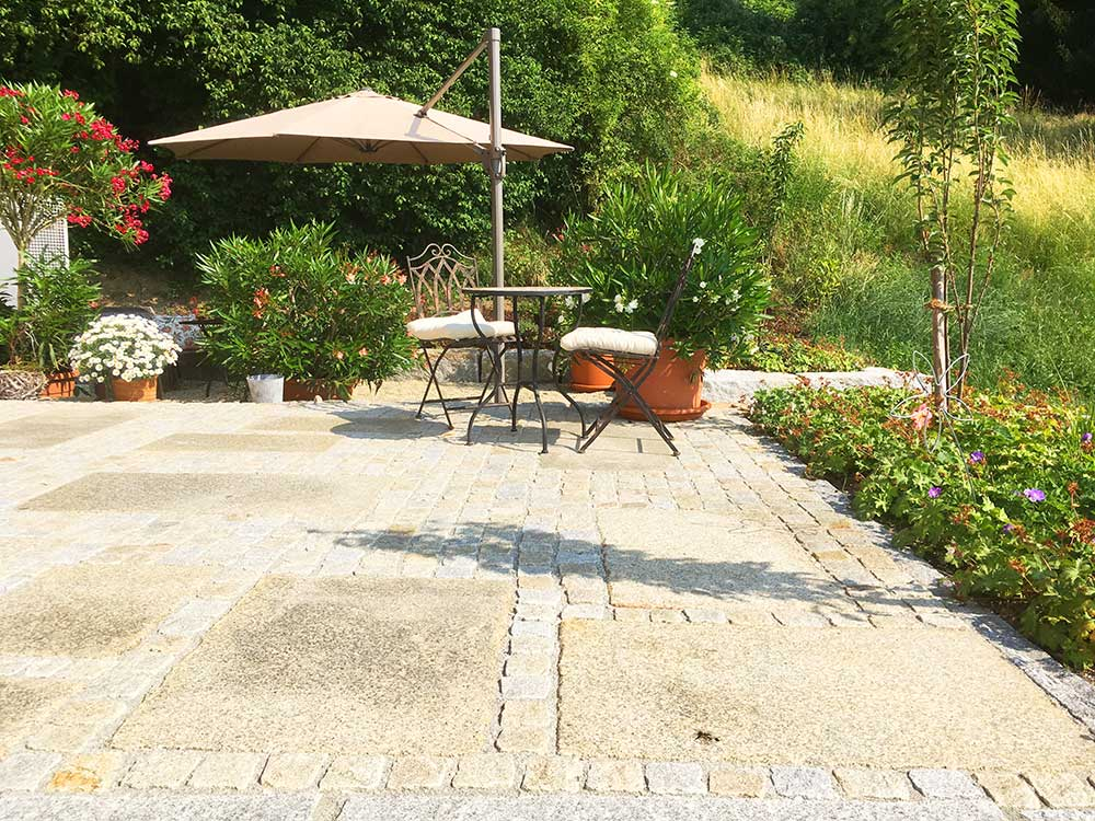 Mediterrane Terrasse mit Gartenmöbeln und Sonnenschirm