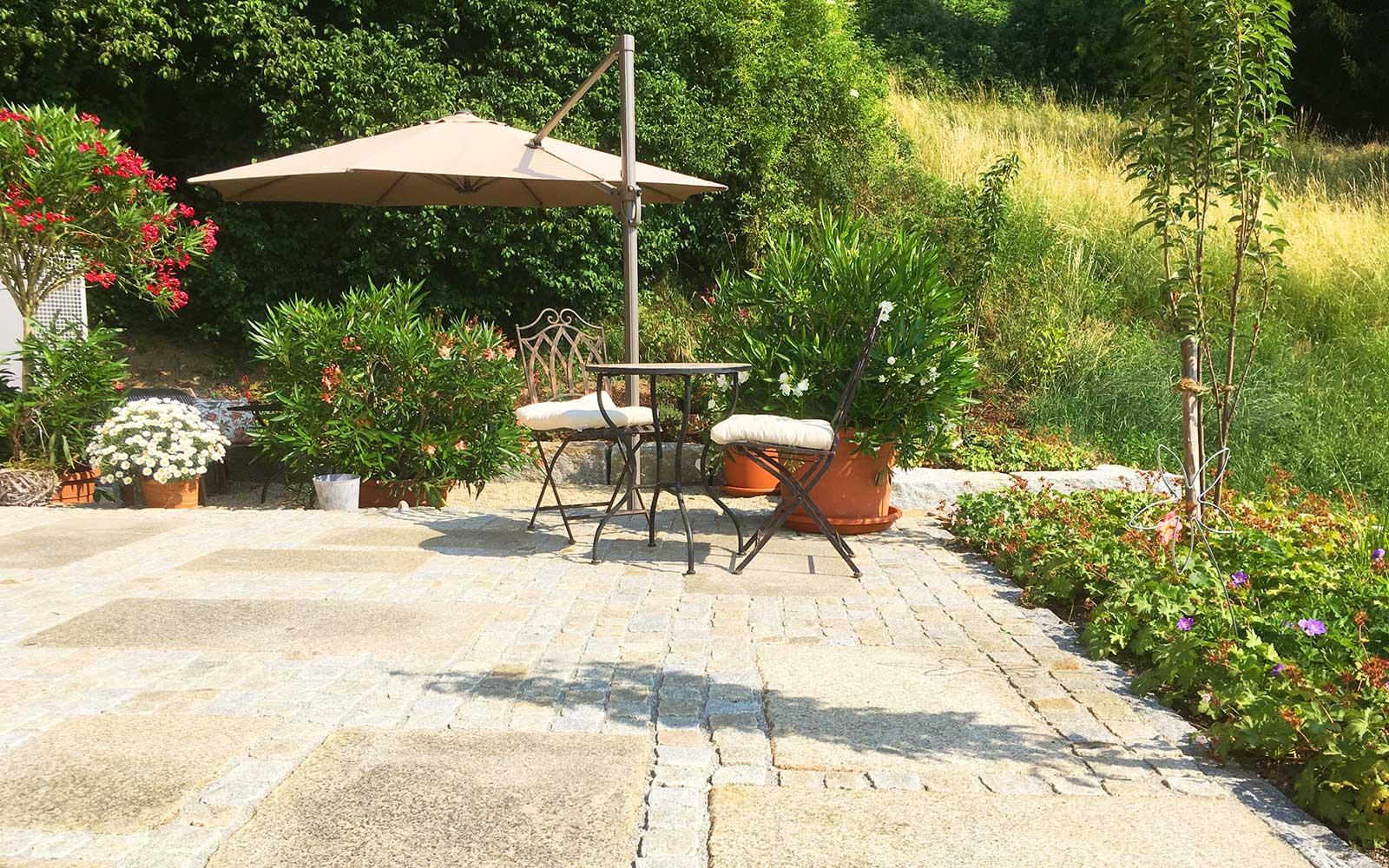 Gepflasterte Terrasse mit Gartenmöbeln und Sonnenschirm