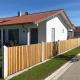 Gartenzaun mit Betonpalisaden und Holzlatten