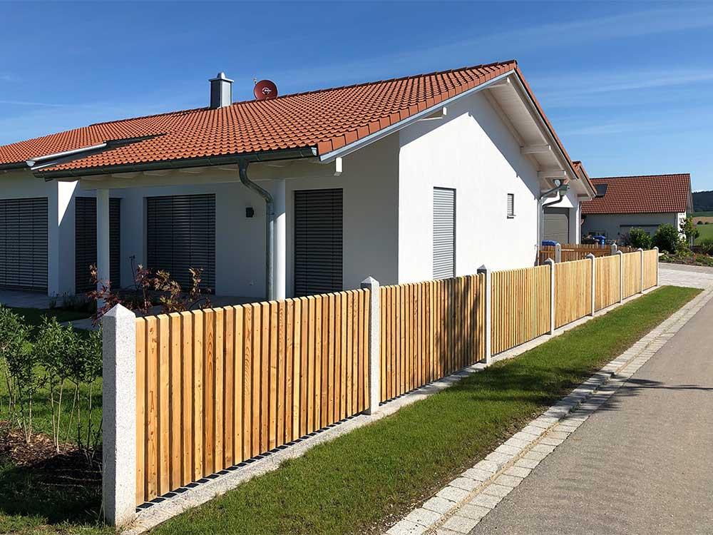 Gartenzaun mit Granitsäulen und Holzlatten