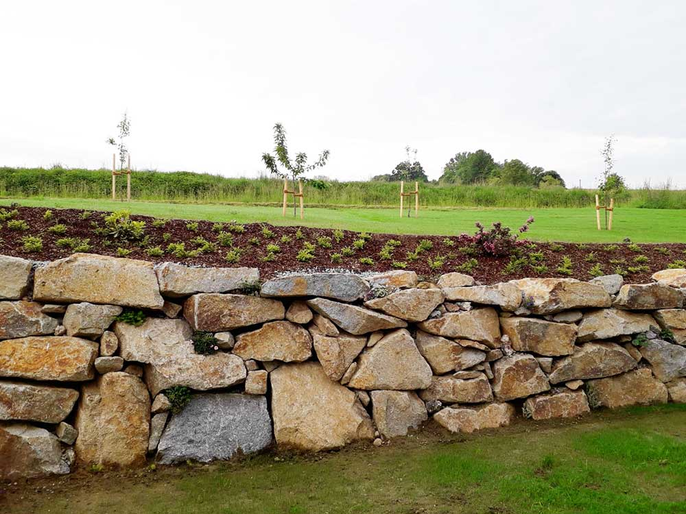 Mauer aus Granitwasserbausteinen