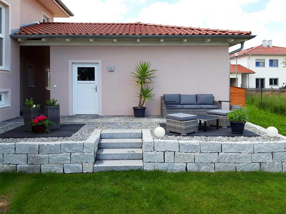 Terrasse mit Mäuerchen und Treppe zum Garten